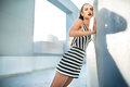 Fashion model in a striped dress near the wall Royalty Free Stock Photo