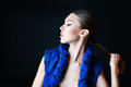 Fashion model with stylish blue make up holding her tail portrait of Royalty Free Stock Image