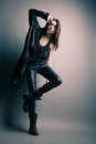 Fashion model wearing leather pants and jacket posing on grey background Royalty Free Stock Photography