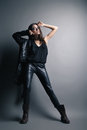 Fashion model wearing leather pants and jacket posing on grey background Stock Photos