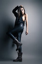 Fashion model wearing leather pants and jacket posing on grey background Royalty Free Stock Photo