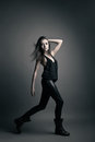 Fashion model wearing leather pants posing on grey background Royalty Free Stock Image