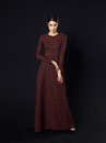 Fashion model wearing long maroon dress on black background Royalty Free Stock Photo