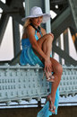 Fashion model in white hat and blue resort dress posing under the bridge at hot summer time Stock Photos