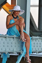 Fashion model in white hat and blue resort dress posing under the bridge at hot summer time Royalty Free Stock Photo