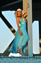 Fashion model in white hat and blue resort dress posing under the bridge at hot summer time Royalty Free Stock Photos