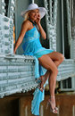 Fashion model in white hat and blue resort dress posing under the bridge at hot summer time Stock Photography