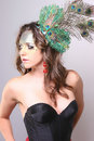 Fashion model with wild makeup with a peacock feat pretty girl and feather in her hair black bustier Royalty Free Stock Image