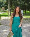 Fashion outdoor photo of beautiful smiling young woman with long hair in luxurious green dress posing for the camera