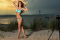 Fashion outdoor photo of sexy beautiful woman with slim fit body in blue bikini posing on the beach at sunset time. Royalty Free Stock Photo