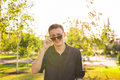 Fashion, people and lifestyle concept - Close-up portrait of happy cheerful confident handsome man in sunglasses in park Royalty Free Stock Photo