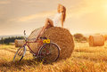 Fashion photo, beautiful woman sitting on a bale of wheat, next to the old bike Royalty Free Stock Photo