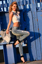 Fashion photo of beautiful young woman model posing on the pier Royalty Free Stock Photo