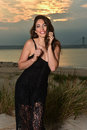 Fashion photo of glamour model in black lace dress posing pretty on the beach. Royalty Free Stock Photo