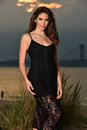 Fashion photo of sexy glamour model in black lace dress posing pretty on the beach. Royalty Free Stock Photo