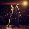 Fashion photo of young beautiful couple men and women snipers holding automatics outdoor Stock Images