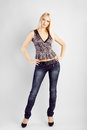 Fashion photo of young magnificent blonde woman wearing jeans and top girl posing studio Stock Photos