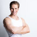 Fashion portrait of attractive smiling man in white shirt with crossed arms poses over wall Stock Photos