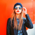 Fashion portrait beautiful blonde woman sends air kiss blowing red lips outdoors wearing sunglasses hat Royalty Free Stock Photo