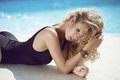 fashion portrait of beautiful tanned woman with blond hair in elegant black bikini relaxing beside blue swimming pool Royalty Free Stock Photo