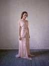 Fashion portrait of beautiful woman in a long pink dress. Royalty Free Stock Photo
