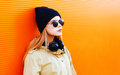Fashion portrait blonde woman with headphones, sunglasses and black hat on a orange colorful background Royalty Free Stock Photo