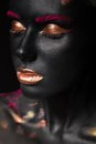Fashion portrait of a dark skinned girl with color make up beauty face picture taken in the studio on black background Royalty Free Stock Photography