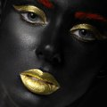 Fashion portrait of a dark skinned girl with color make up beauty face picture taken in the studio on black background Stock Images