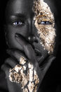 Fashion portrait of a dark-skinned girl with gold