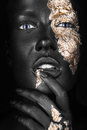 Fashion portrait of a dark-skinned girl with gold Royalty Free Stock Photo
