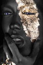 Fashion portrait of a dark-skinned girl with gold make-up. Beauty face. Royalty Free Stock Photo
