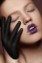 Fashion portrait of expression model with bright lips make-up, black palm greasepain Royalty Free Stock Photo