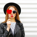 Fashion portrait face pretty sweet young woman with red lips making air kiss with lollipop heart wearing black hat leather jacket