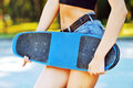 Fashion portrait of female hands holding a skateboard closeup outdoors Royalty Free Stock Image