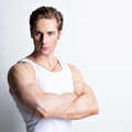 Fashion portrait of handsome young man in white shirt with crossed arms poses over wall Royalty Free Stock Photos