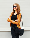 Fashion portrait happy smiling woman wearing sunglasses jacket and black handbag clutch over grey Royalty Free Stock Photo