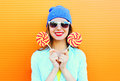 Fashion portrait happy smiling young woman with a lollipop on stick over colorful orange Royalty Free Stock Photo