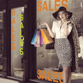 Fashion portrait of kitsch shopping girl in front of window shop blonde woman posing and taking some colorful bags she wearing Royalty Free Stock Photos