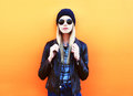 Fashion portrait pretty blonde woman in rock black style on a colorful orange background Royalty Free Stock Photo