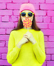 Fashion portrait pretty cool girl having fun with lollipop over pink Royalty Free Stock Photo