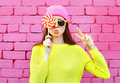 Fashion portrait pretty cool girl with lollipop having fun over pink background Royalty Free Stock Photo