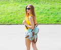 Fashion portrait of pretty cool girl wearing a sunglasses and backpack outdoors in summer day Stock Photos