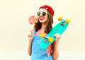 Fashion portrait pretty cool smiling girl with a lollipop and skateboard over white Royalty Free Stock Photo