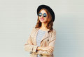 Fashion portrait pretty happy smiling woman with crossed arms wearing a black hat sunglasses over grey Royalty Free Stock Photo