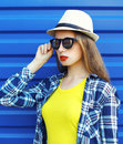 Fashion portrait of pretty stylish girl in sunglasses, straw hat and plaid shirt over blue Royalty Free Stock Photo