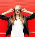 Fashion portrait pretty stylish woman with red lipstick wearing a rock black jacket and sunglasses Royalty Free Stock Photo
