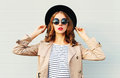 Fashion portrait pretty woman with red lips wearing a black hat sunglasses over grey Royalty Free Stock Photo
