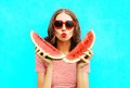 Fashion portrait pretty young woman is holding slice of watermelon and blowing lips