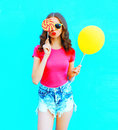 Fashion portrait pretty young woman wearing pink t-shirt, denim shorts with yellow air balloon, lollipop candy over colorful blue Royalty Free Stock Photo