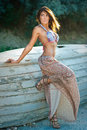 Fashion portrait of sexy brunette girl in swimsuit leaning on a wooden boat sensual attractive woman with long skirt posing Royalty Free Stock Images